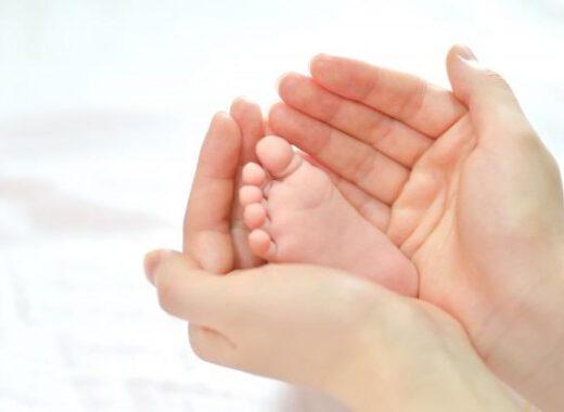 Manos abrazando el pie de un bebé